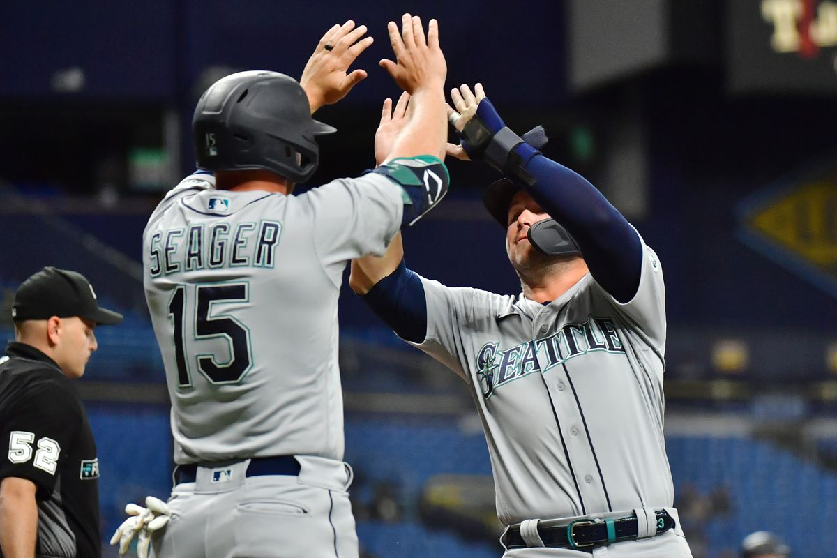 Kyle Seager #15 celebrates with Ty France #23 of the Seattle Mariners after both scored in the third inning against the Tampa Bay Rays at Tropicana Field on August 02, 2021 in St Petersburg, Florida.