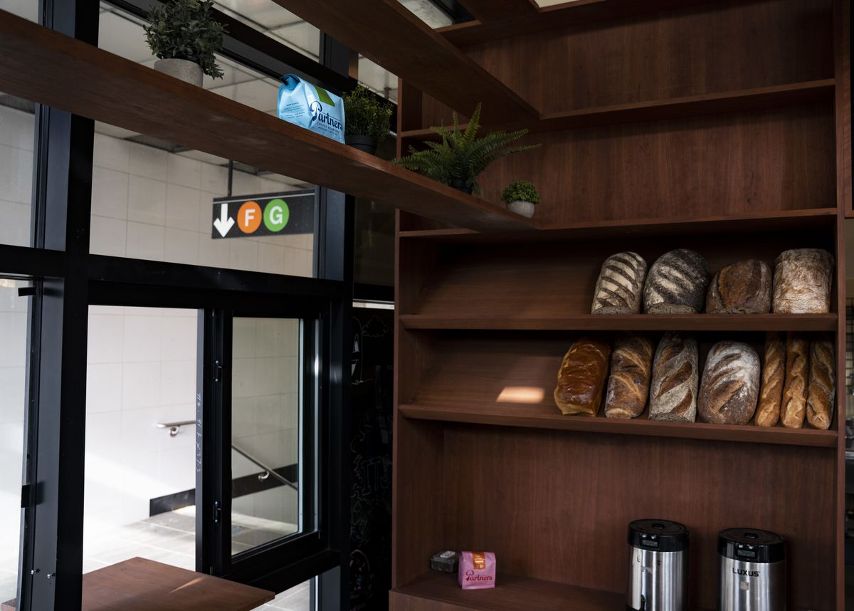 Baguette and loaves of homemade bread line the shelves of a cafe. Coffee canisters are visible below them, while a New York City subway station sign can be seen outdoors.