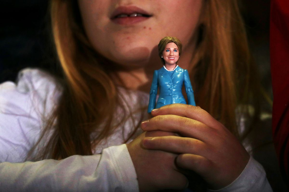 A young supporter holds a Hillary Clinton doll during a campaign rally in Pittsburgh, Pennsylvania.