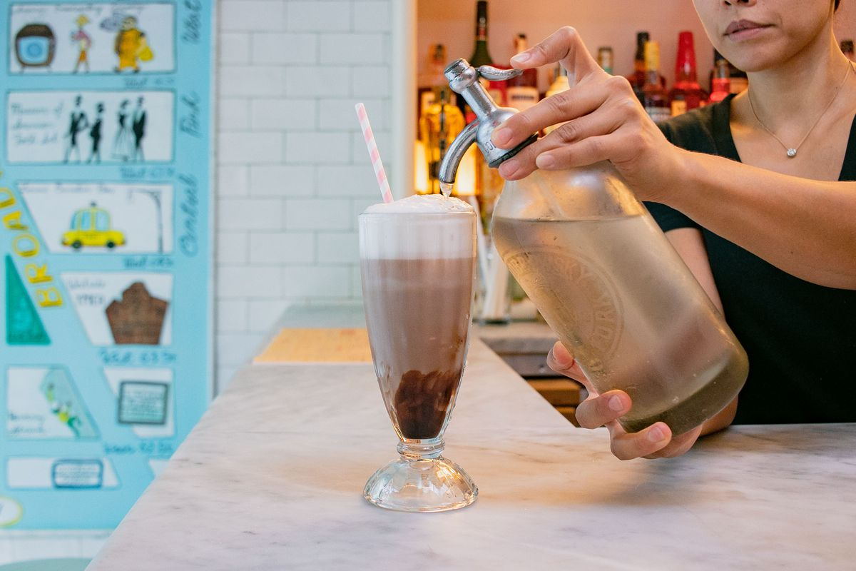 A person holds a bottle of carbonated water and pours some of it into a brown drink with white foam on top and a red and white straw sticking out of the side