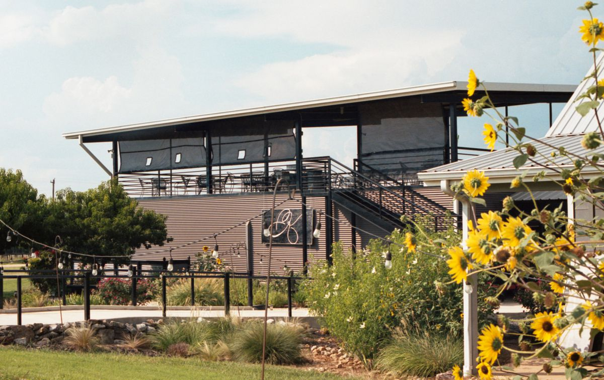 A two-story building with tables and chairs and mesh sunshades on the roof, with yellow sunflowers in the foreground on the right.