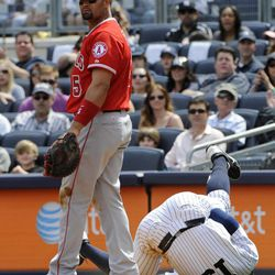 New York Yankees' Alex Rodriguez, right, is safe on a fielder's choice as  Los Angeles Angels first baseman Albert Pujols looks on during the first inning of a baseball game Saturday, April 14, 2012 at Yankee Stadium in New York.