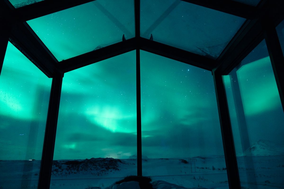 Glass cabin with view of glowing blue-green lights in the sky.