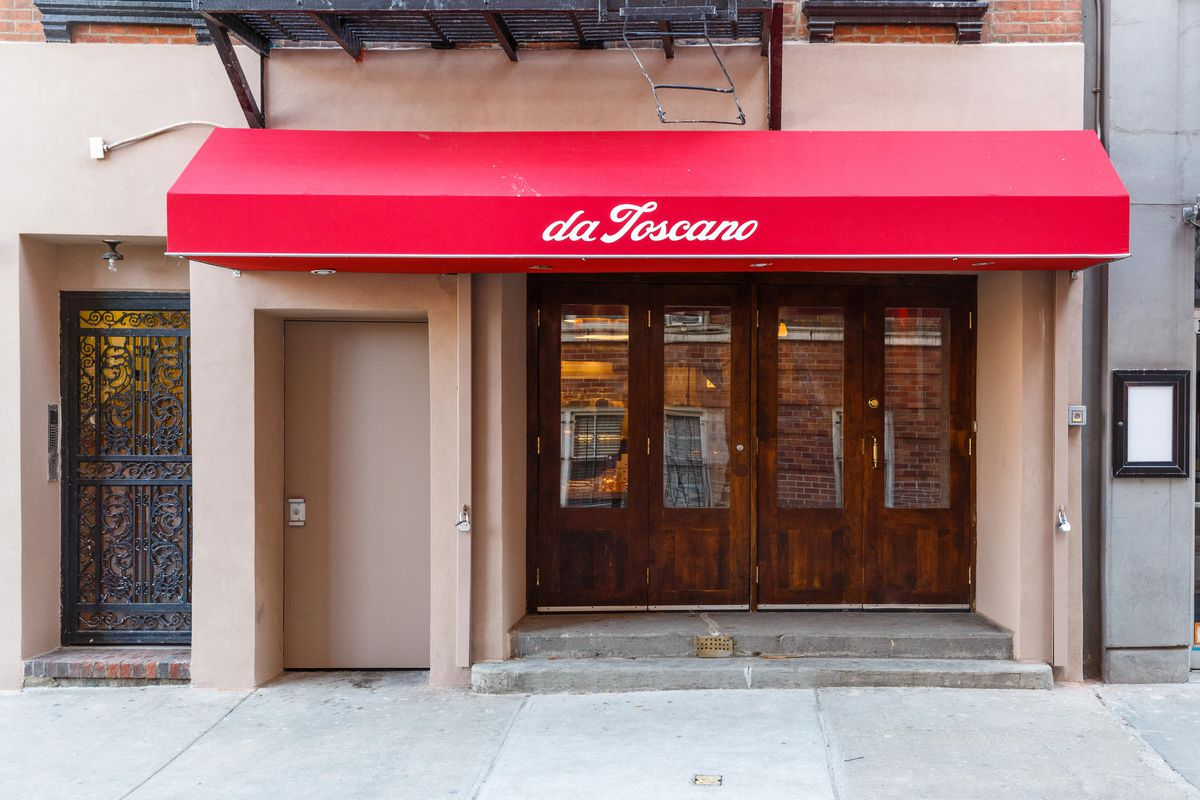 A red owning indicates the entrance to a restaurant with double wooden doors and long glass windows