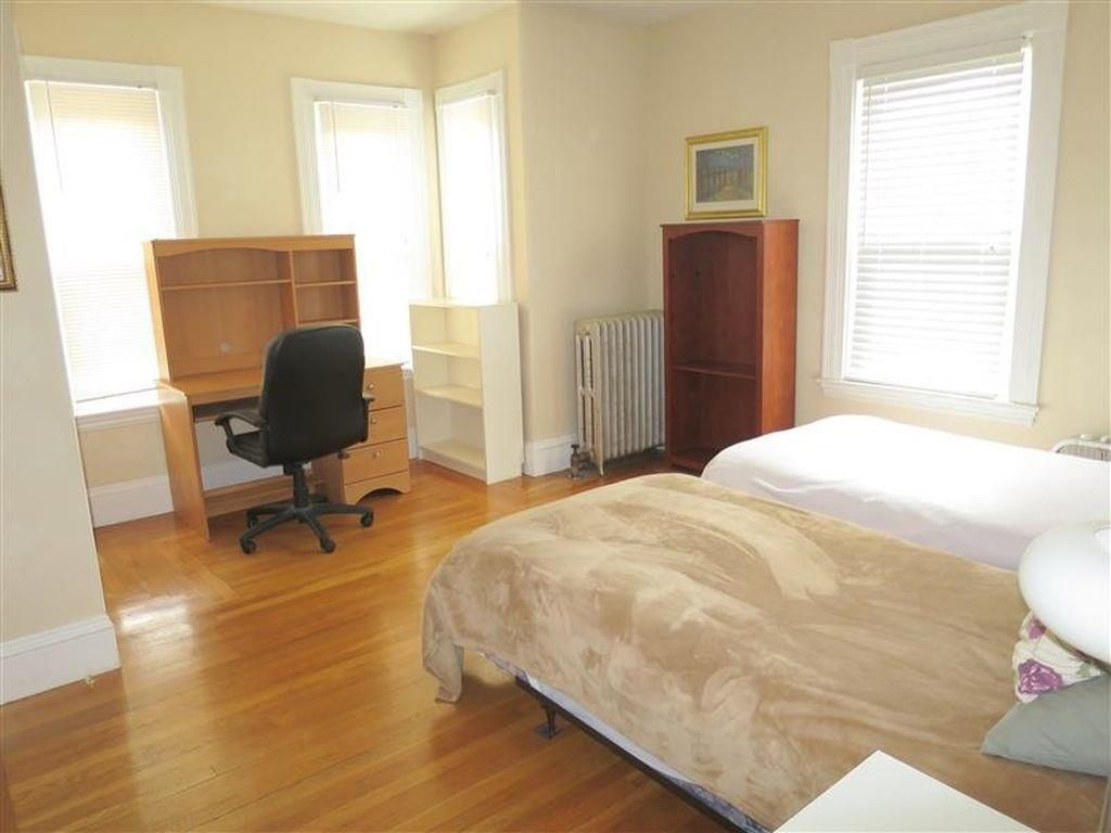 A bedroom with two twin beds and a desk with a chair.