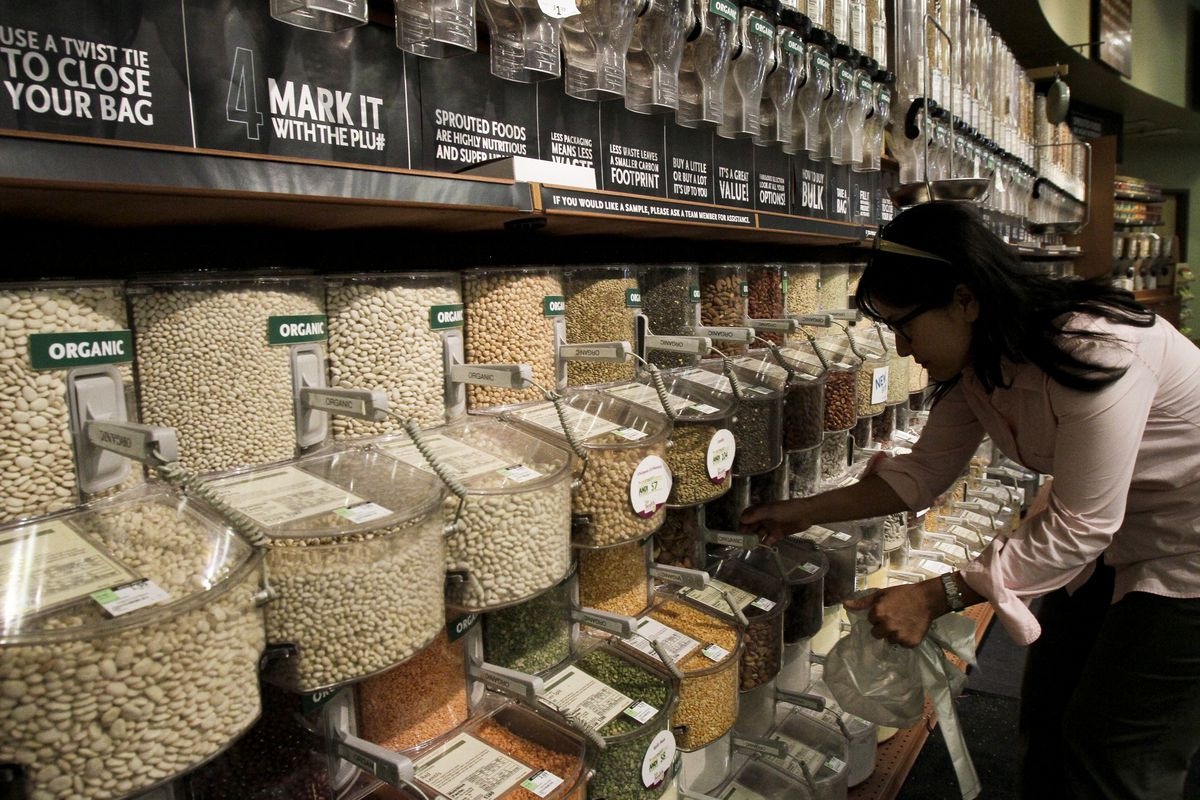 A woman scoops from the bulk bins at the Whole Foods Market in Pasadena.