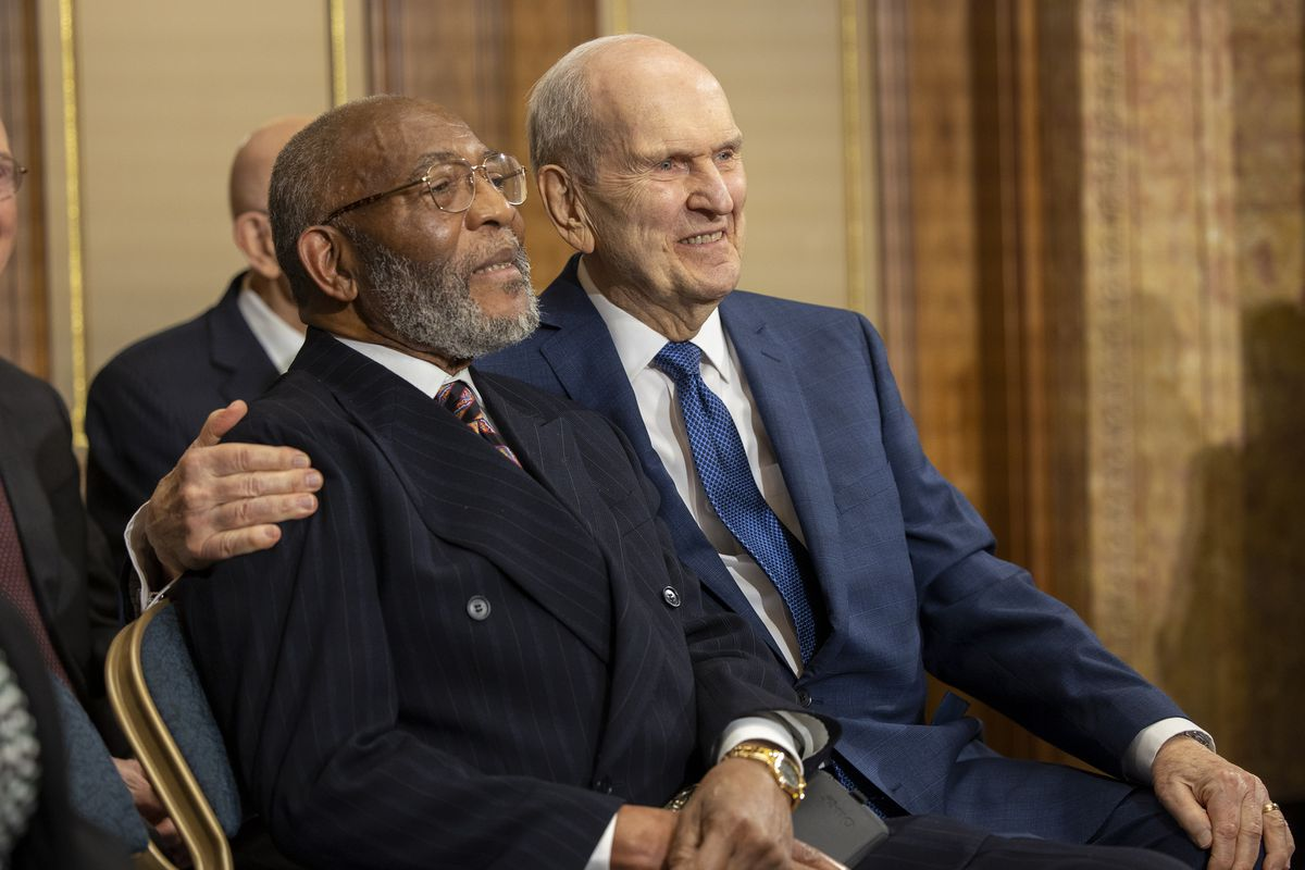 President Russell M. Nelson, a Latter-day Saint leader, sits with his arm around the Rev. Amos C. Brown of the NAACP.