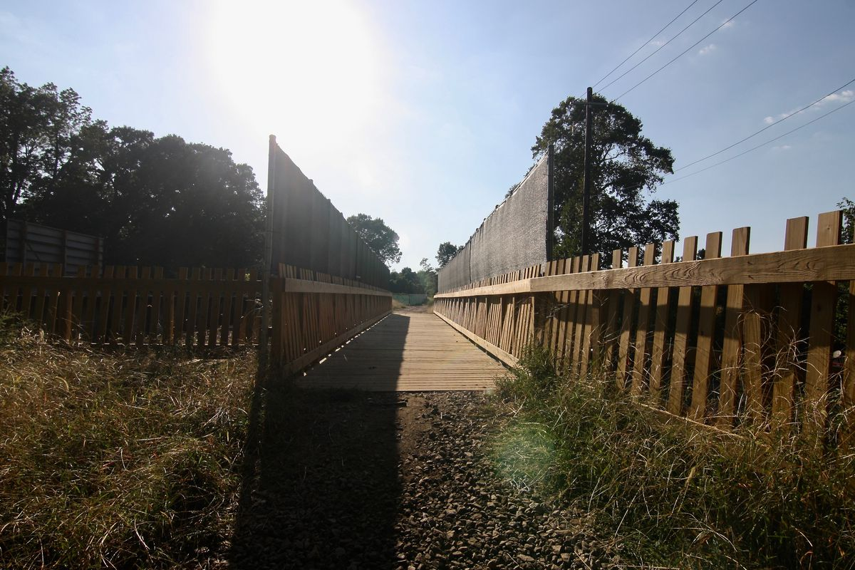 A wooden bridge with sun setting behind it and weeds on both sides.