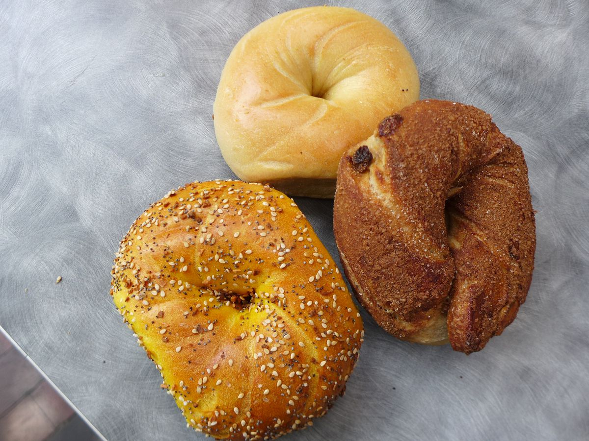 Three bagels, one crusted with cinnamon, on a gray tabletop.