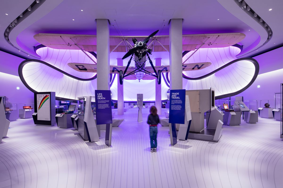 Interior shot of gallery with hanging aircraft and large curving ribbons floating above exhibition space.