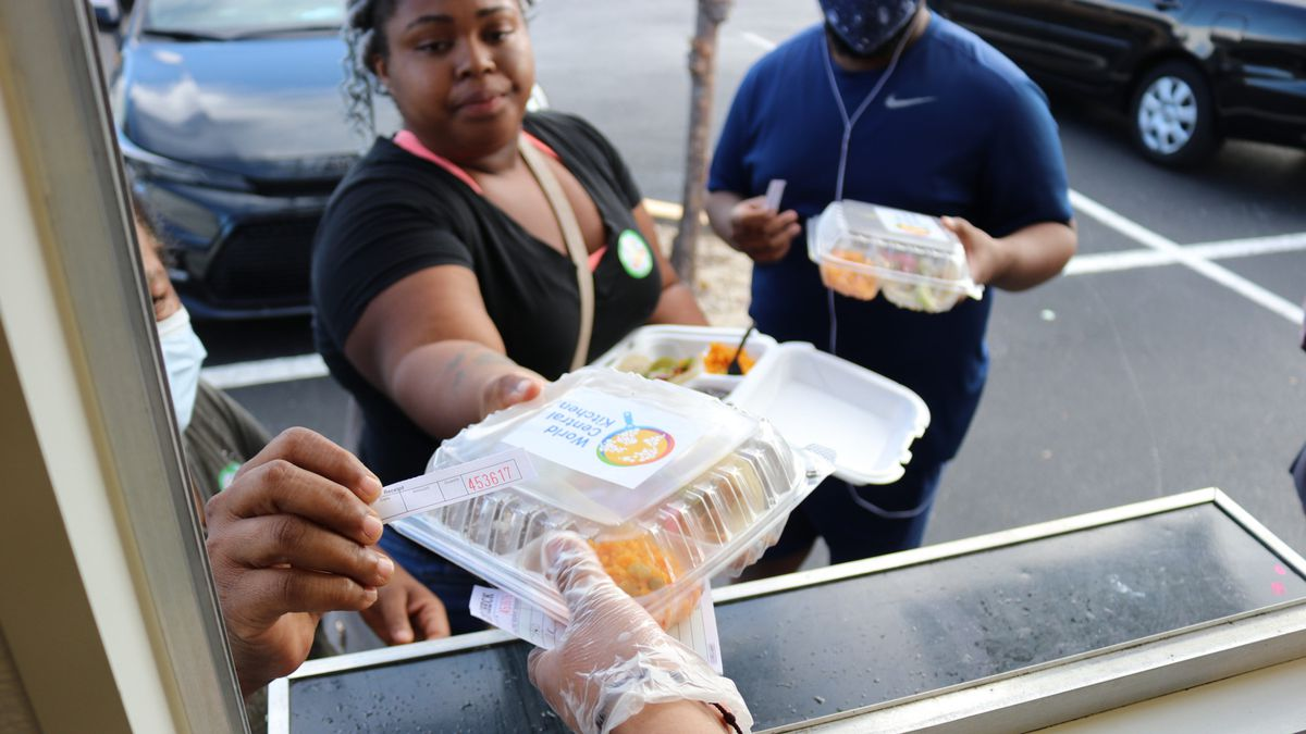 Gloved hand handing a boxed meal to voters from the window of a food truck.