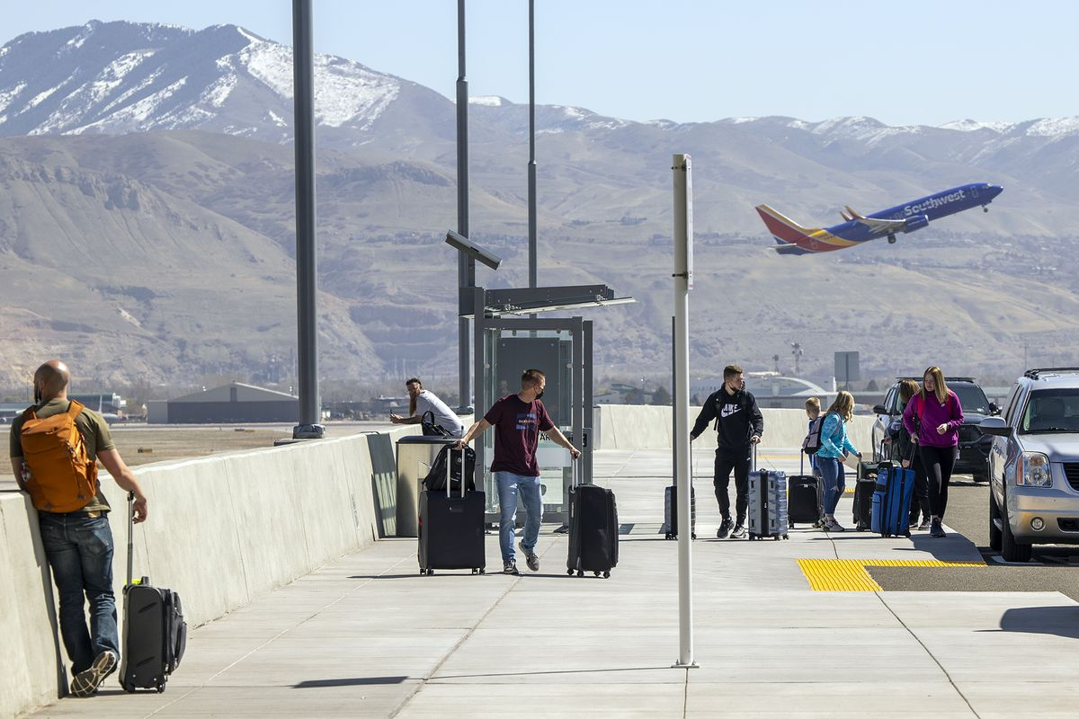 Travelers arrive for flights as a Southwest Airlines plane takes off at the Salt Lake City International Airport on Friday, April 2, 2021.