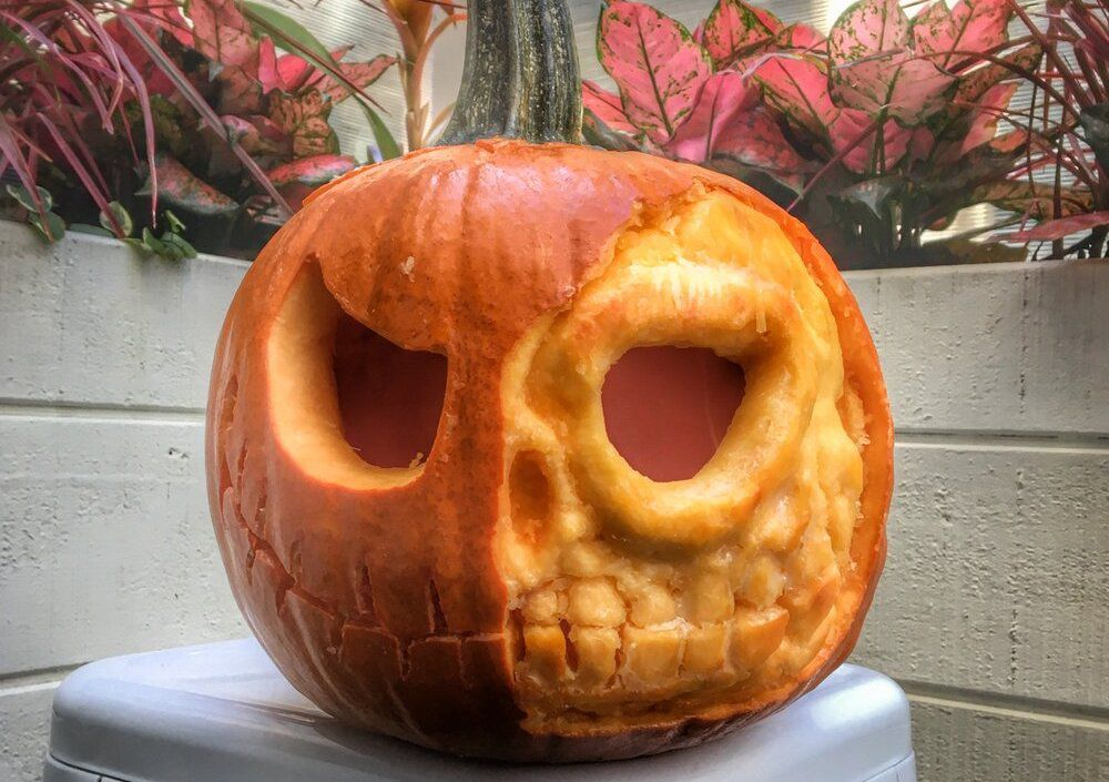 An orange pumpkin with a skull carved into the front is placed on a metal stool with wooden flower planter boxes in the background