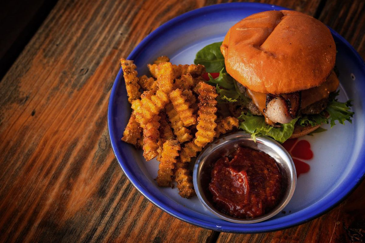 A cheeseburger and fries served on a white plate with blue rim. A metal cup of red dipping sauce sits to the side.