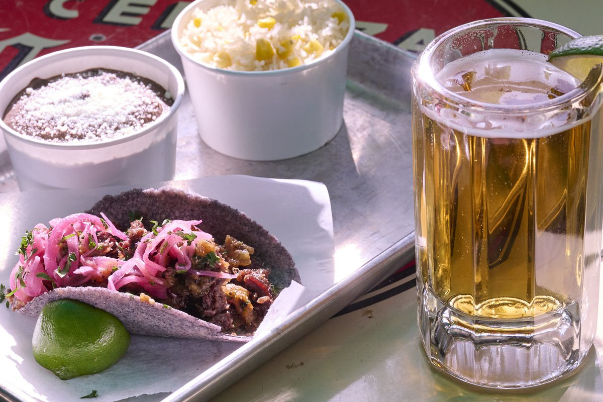 A taco on a blue corn tortilla, a small cup of beans and another of corn and cheese, all on a metal tray, and a large beer