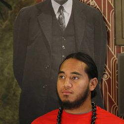 """Hameti Lomu is framed by a photo of former LDS President Heber J. Grant as he helps check people in at the Pacific Islander conference """"Navigating the Future"""" sponsored by the Deseret News as a forum for different issues for Polynesians at the Joseph Smith Building Wednesday, Sept. 21, 2011, Salt Lake City, Utah."""