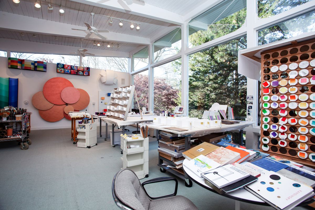 An artist studio has one wall of glass, tall ceilings, and desks with paint and color walls.