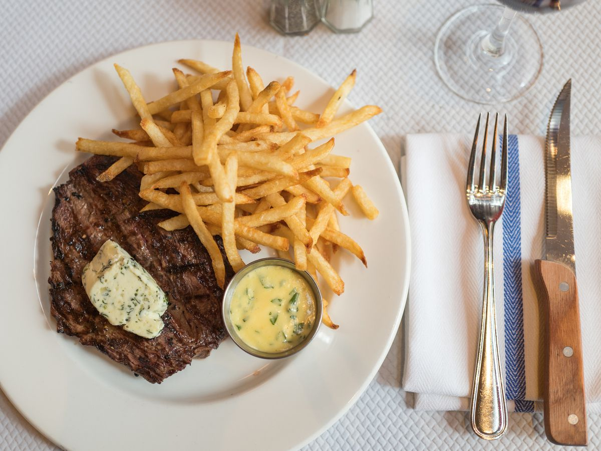 Steak frites on a white plate with a fork and knife next to it