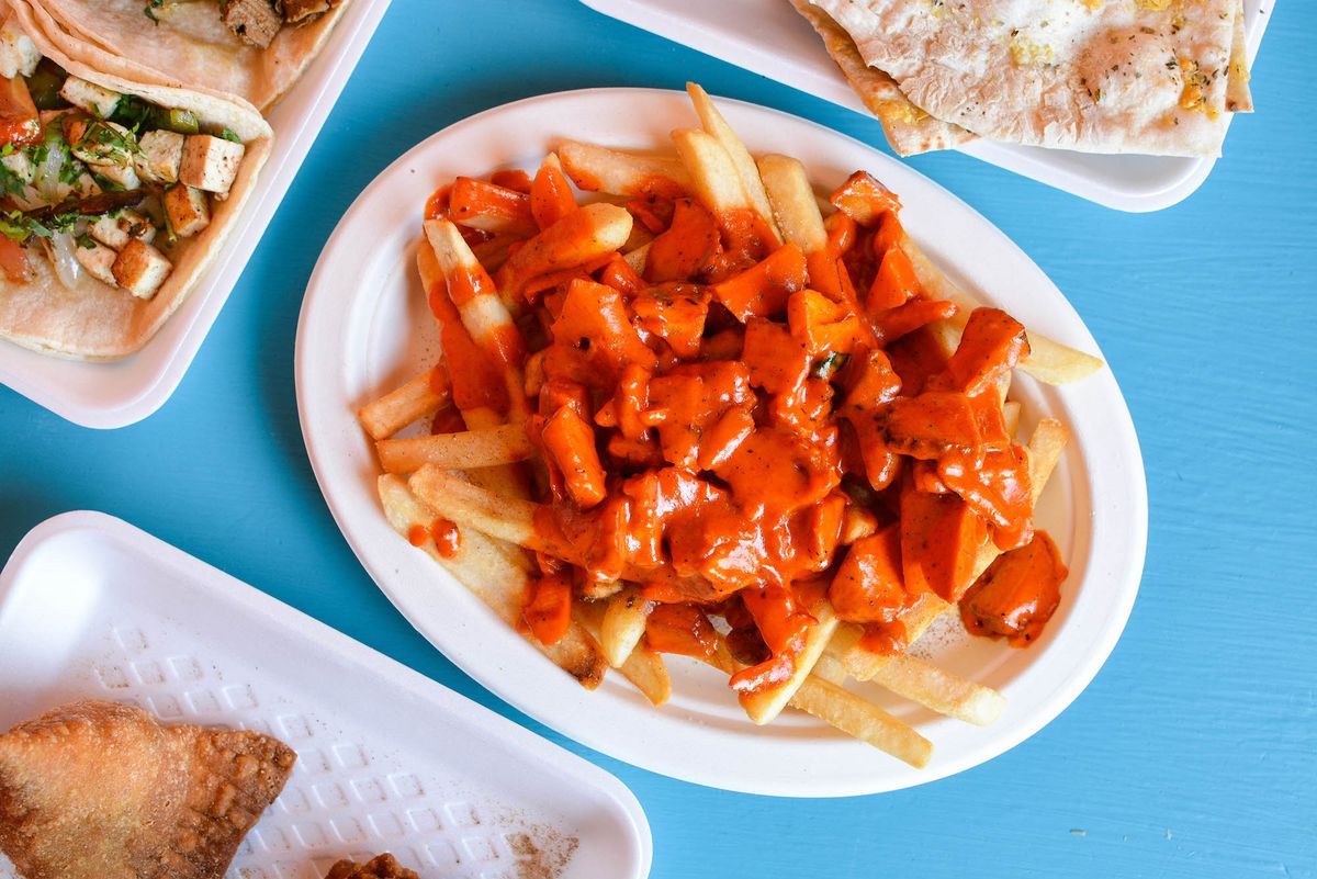 A blue table with bright orange tikka masala sauce over fries.