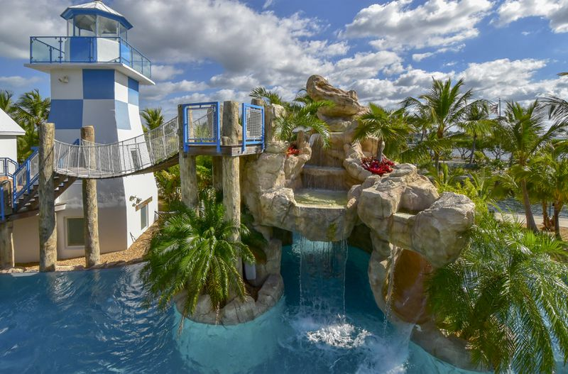 A resort-style pool area with rocks, palm trees, and a suspension bridge that leads to a lighthouse.