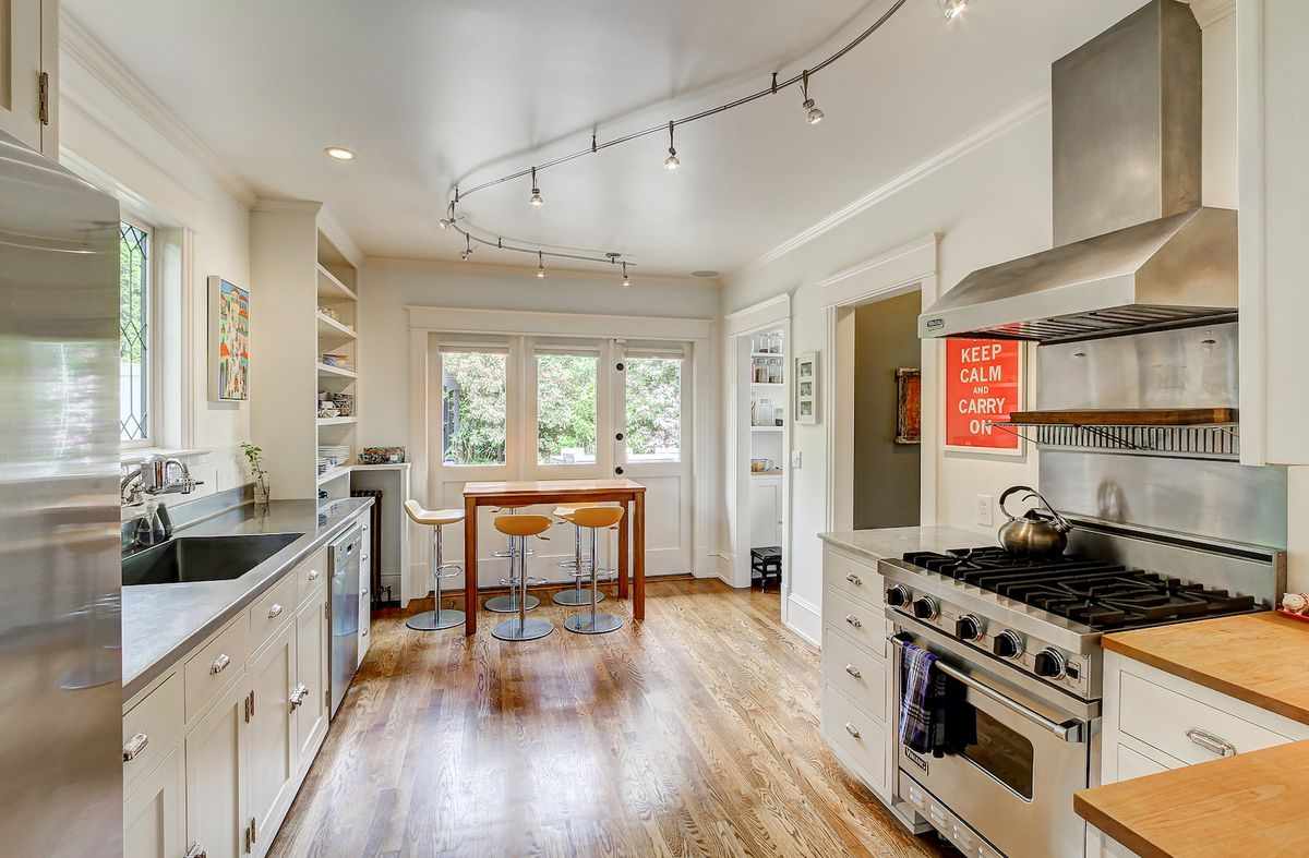A kitchen with doors in the back, track lighting above, and hardwood floors.