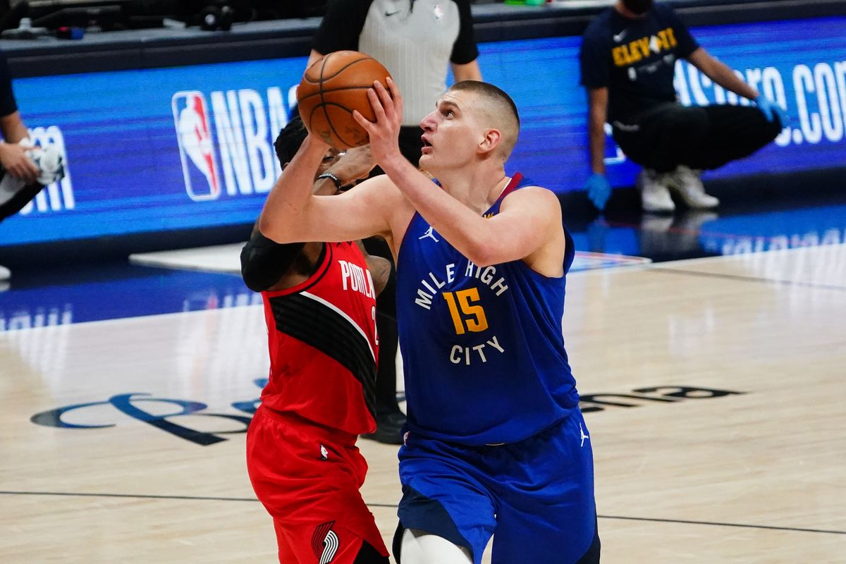 Denver Nuggets center Nikola Jokic shoots the ball past Portland Trail Blazers guard CJ McCollum in the second quarter during game one in the first round of the 2021 NBA Playoffs