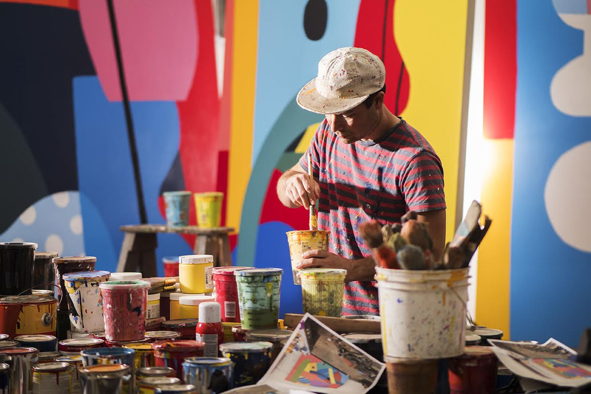 A man mixes paint in front of a colorful backdrop.