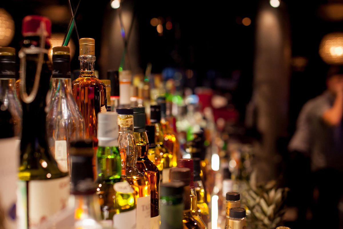 A dimly-lit bar showcasing gleaming bottles of liquor