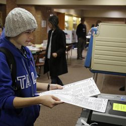 Baldwin Wallace University student Calla Bufford, from Scranton, Pa., feeds her ballot into a scanner at a polling site on campus in Berea, Ohio Tuesday, Nov. 6, 2012. Bufford said she was voting in her first presidential election.