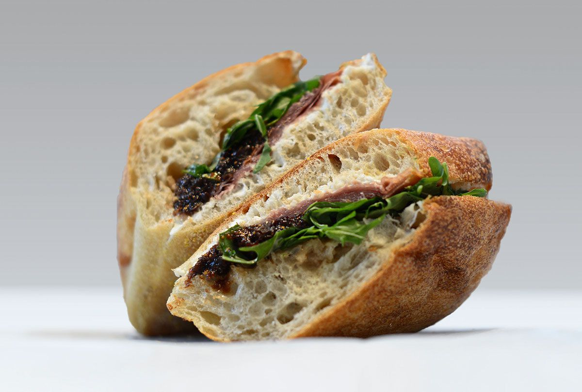 A fig and prosciutto sandwich, cut in half, is isolated on a light background.