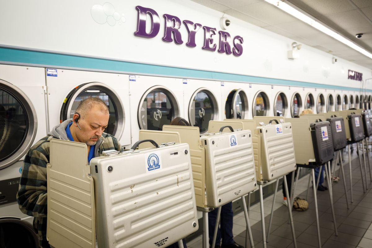 An older white man votes in an electronic polling booth at a laundry mat.