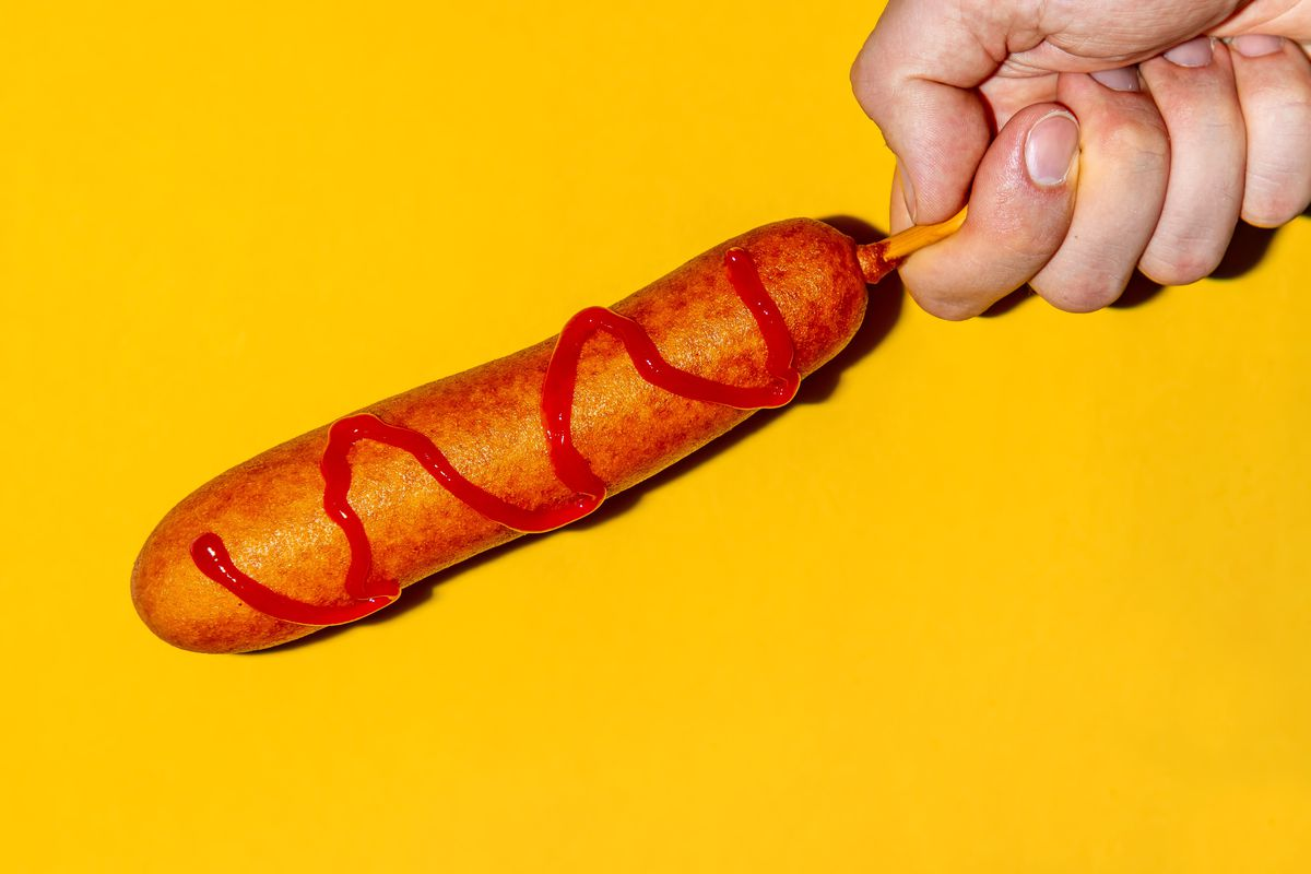 A hand holding a corn dog against a yellow background