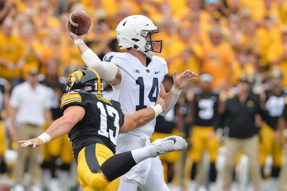 Penn State Nittany Lions quarterback Sean Clifford throws a pass as Iowa Hawkeyes defensive end Joe Evans rushes in during the first quarter at Kinnick Stadium.