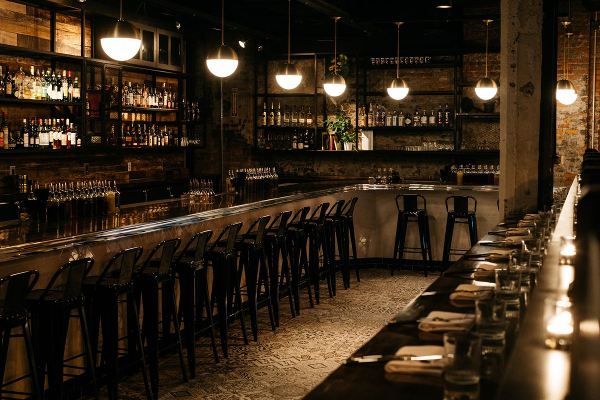The bar at Grey Ghost is concrete with black metal stools and pendant lights.