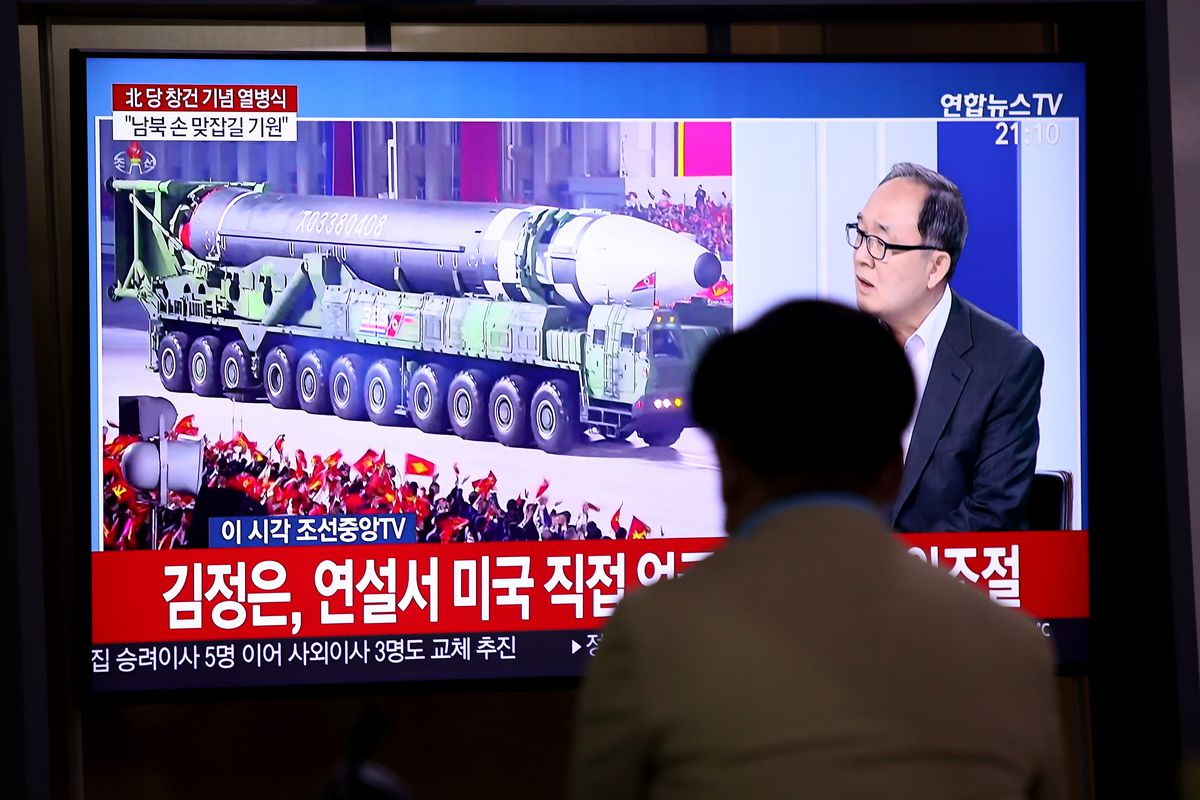 A man watches a television showing North Korea's military parade