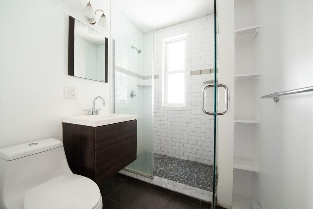 A bathroom with a glass-enclosed shower.