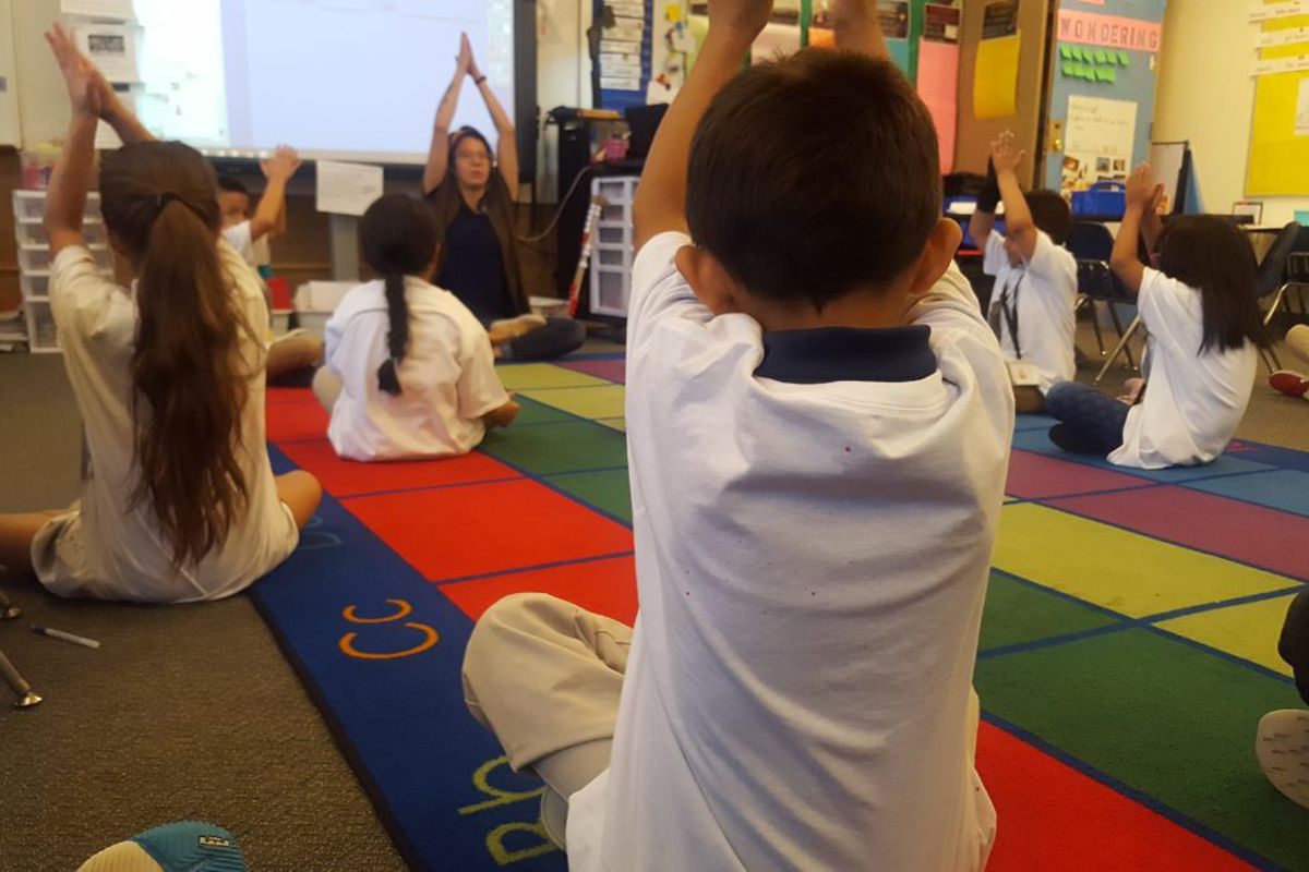 First graders do yoga during class Sept. 20, at Elkhart Elementary in Aurora.