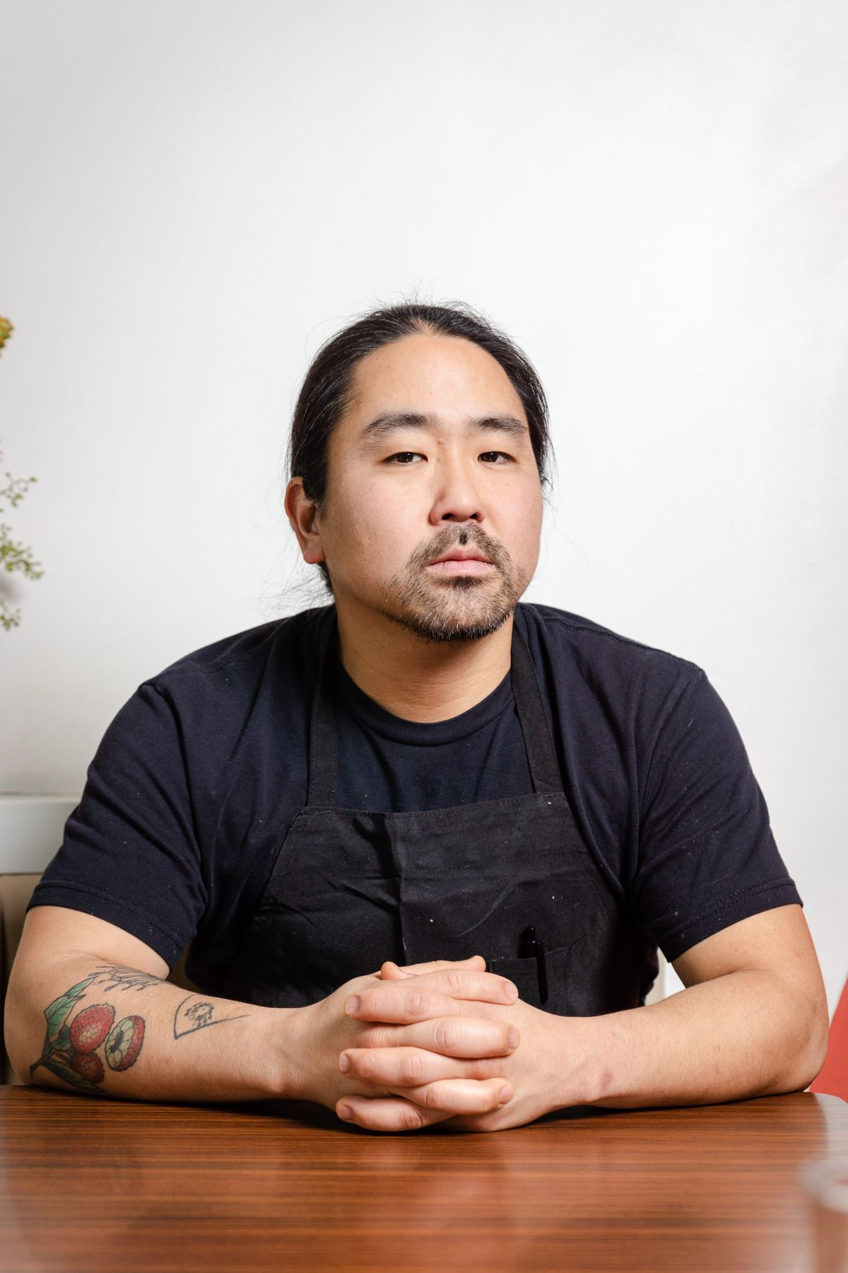 Colin Yoshimoto, the chef de cuisine at Eem, stares with a blank face at the camera. He sits at a table, not smiling, with his long hair pulled back behind him. He's wearing a black apron, with a colorful tattoo of a flower on his arm.