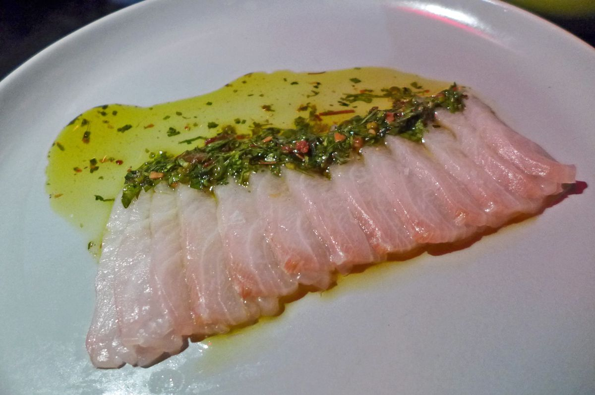 Slices of fish neatly lined up and overlapping in glistening oil.