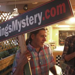 """In this July 19, 2011 photo, Hank Black, left, holds a sign as he talks with Michael Cangemi  after a meeting of the North Texans for 9/11 Truth group at a cafe in Dallas. Nationwide, the skeptics, who prefer the term """"9/11 truth activists"""" instead of the moniker """"truthers,"""" generally have about a dozen beliefs surrounding what happened on that day, although there are some variations on who was responsible for the attacks and why. Among the beliefs: that the World Trade Center buildings could never have collapsed due to fire, that the buildings were brought down by explosives, that there were warnings of the impending attacks from 11 different countries and that fighter jets could have intercepted at least one of the four planes that day. Many believe that there were criminal elements within the government that caused the attacks."""