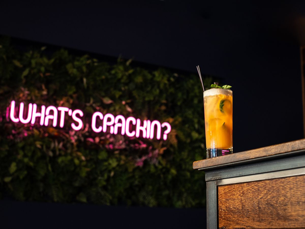 """An orange cocktail in a tall glass sits at the edge of a table in front of wall of green plants and a pink neon sign that reads, """"What's Crackin'"""""""