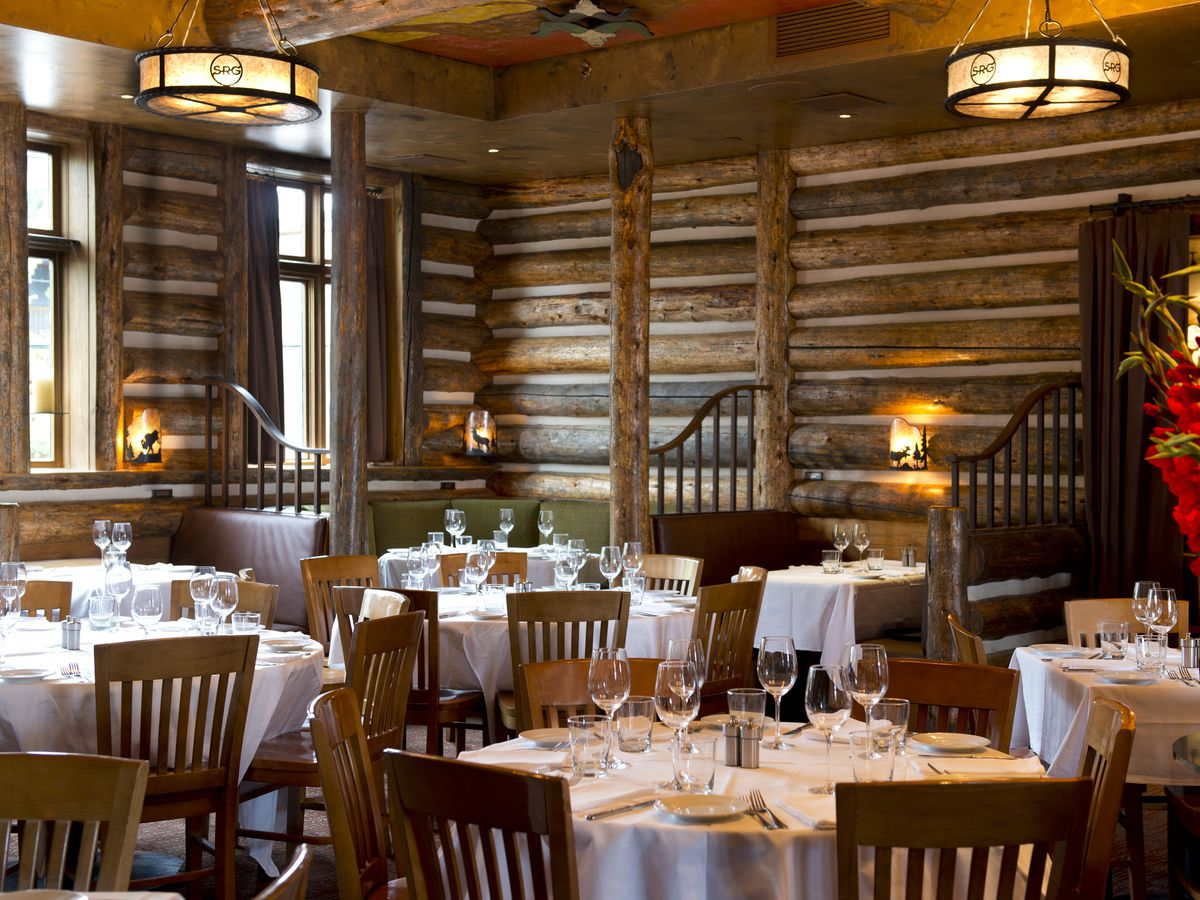 A wood-paneled interior with tall windows, large paper-covered pendant lights, and white tablecloth-covered tables