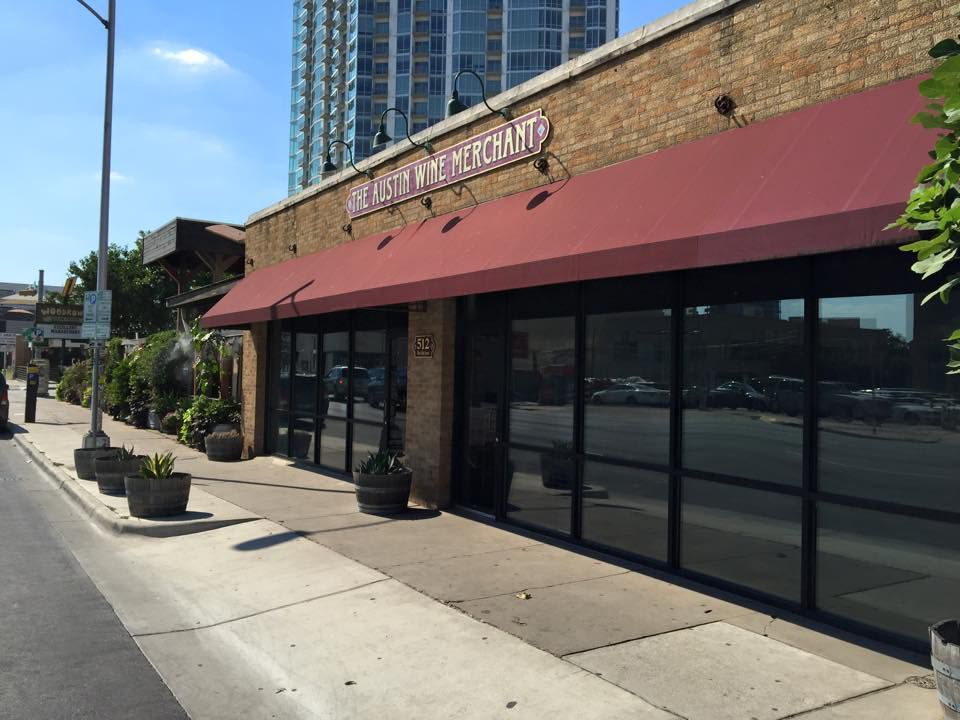 """The facade of a brick retail store ith tall windows, a red awning, and sign that reads """"Austin Wine Merchant"""""""
