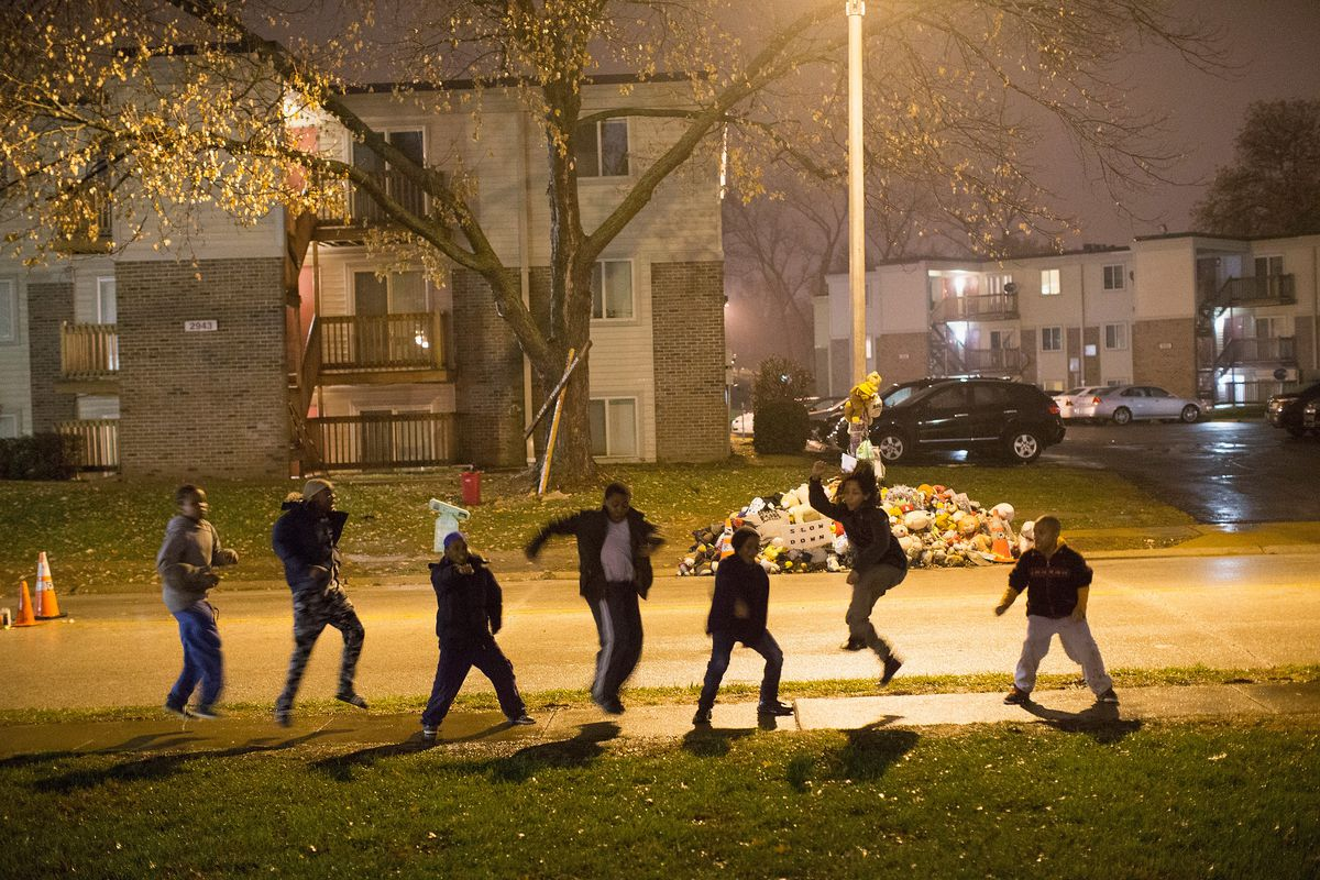 Young people break dance near a memorial of Michael Brown at the scene of the black teen's police shooting death.