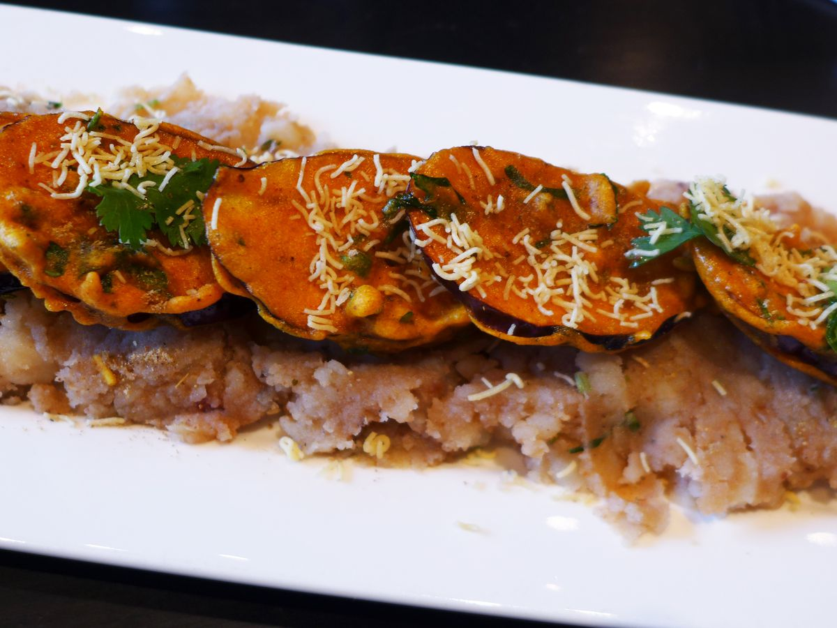 Segments of eggplant with a reddish coating are aligned on top of a long low mound of mashed potatoes.