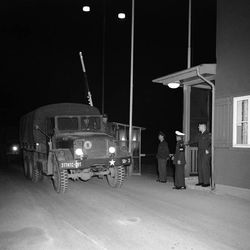 The first of four U.S. Army trucks, detained by Soviet authorities for 54 hours when the Americans refused to have their vehicles inspected, leads the way into West Germany at the Helmstedt check point after release on Feb. 2, 1959. CPL. Richard Masiero of Stockbridge, Mass., the convoy commander, rides the running board to the driver's left as the trunk rolls past two U.S. Military policemen and a West German border guard.