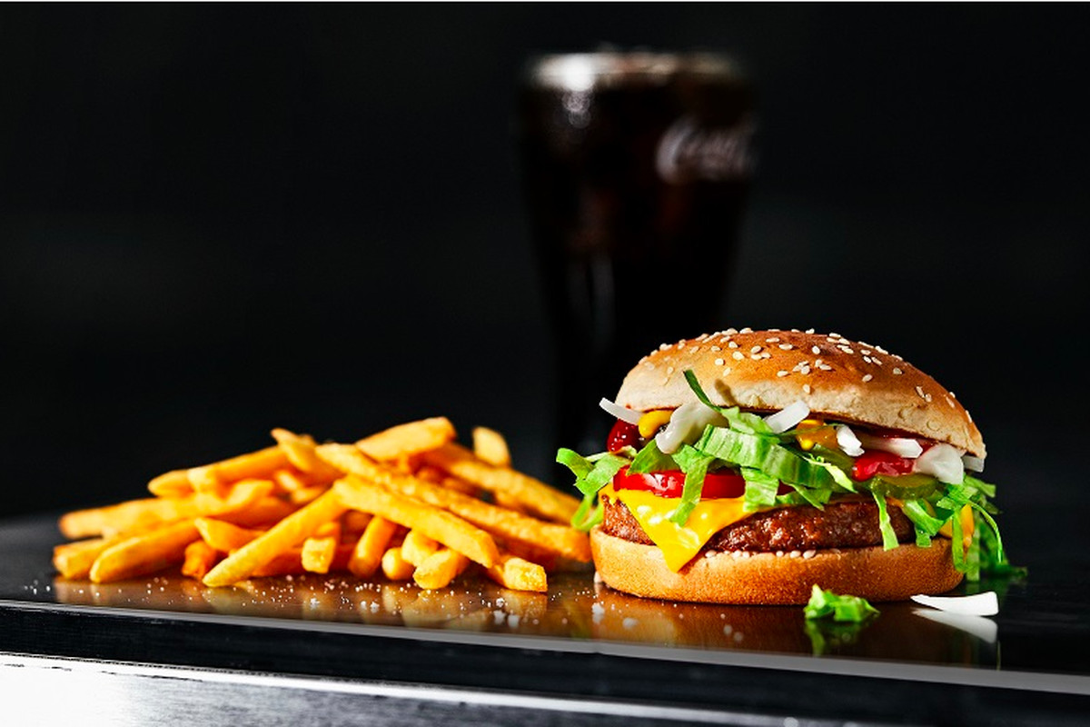 A photo of a burger, french fries, and a soda in front of a black background.