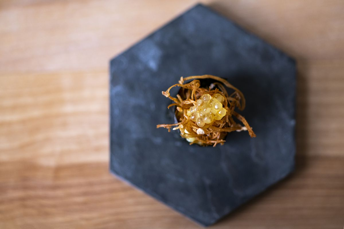 Vue à vol d'oiseau d'un nigiri aux champignons râpé garni de œufs, sur une assiette à six faces.