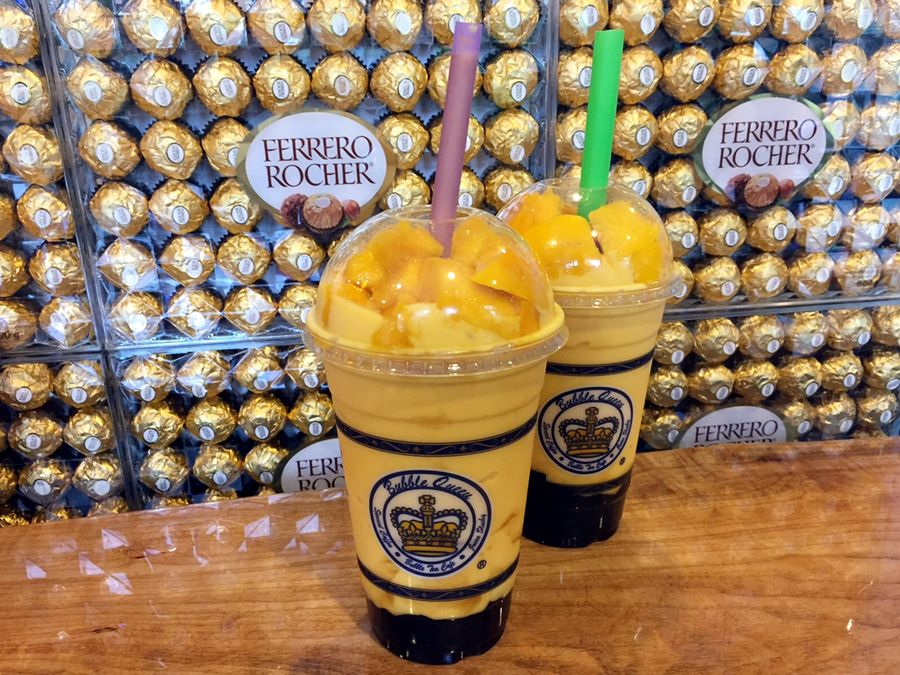 Two cups of mango slushes with tapioca balls at the bottom against a backdrop of Ferrero Rocher chocolates.
