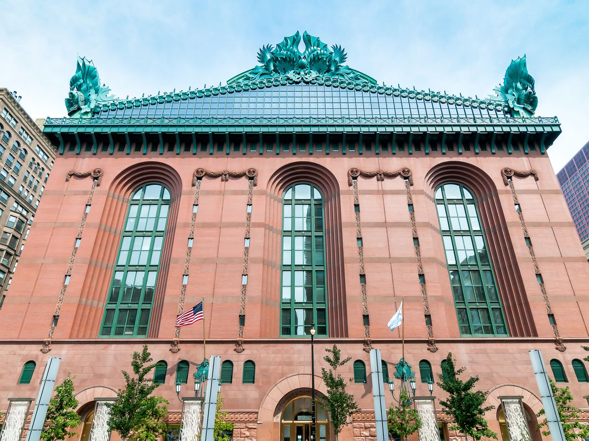 A brick building with an ornate copper roof that's turned turquoise.